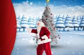 Composite image of santa pulls something with a rope — Stockfoto