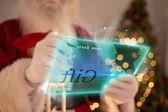 Composite image of santa using futuristic touchscreen — Stock Photo