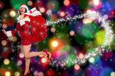 Composite image of woman standing with christmas presents — Stock Photo