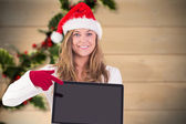 Composite image of festive blonde pointing to laptop — Stok fotoğraf