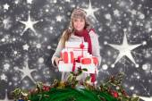 Composite image of happy blonde in winter clothes holding gifts — Stock Photo