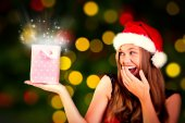 Composite image of festive blonde holding a gift bag — Fotografia Stock