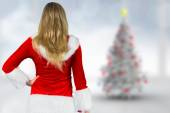 Composite image of pretty girl in santa outfit holding gift — Stock Photo