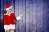 Pretty santa girl presenting with hand — Stock Photo