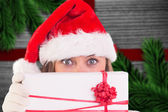 Composite image of festive blonde holding a gift — Stockfoto