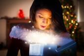 Imagen compuesta de atractivo regalo de apertura de niña santa — Foto de Stock