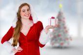 Composite image of pretty girl in santa costume holding gift box — Stock Photo