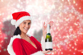 Composite image of woman holding a champagne bottle — Stok fotoğraf