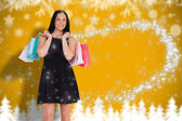 Composite image of woman walking with shopping bags — Stock Photo