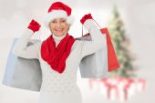 Composite image of festive woman holding shopping bags — Stock Photo
