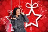 Composite image of smiling woman holding shopping bag — Stock Photo