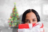 Composite image of woman holding a present — Stock Photo