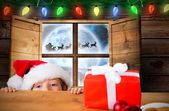 Composite image of festive boy peeking over table — Stok fotoğraf