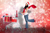 Composite image of woman standing with shopping trolley — Stock Photo