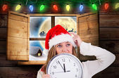 Composite image of festive blonde showing a clock — Stok fotoğraf