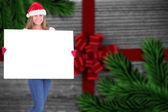 Composite image of festive blonde holding a poster — Stock Photo