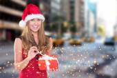 Composite image of festive blonde opening a gift — Stock Photo
