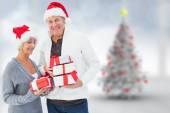 Festive mature couple holding christmas gifts — Stock Photo