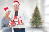 Composite image of festive mature couple holding christmas gifts — Stock Photo