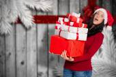 Composite image of woman holding many christmas presents — Stock Photo