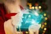 Composite image of santa using futuristic touchscreen — 图库照片