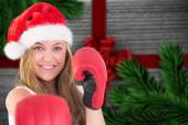 Composite image of festive blonde punching with boxing gloves — Stock Photo