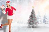 Composite image of woman smiling with christmas present — Stok fotoğraf