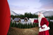 Composite image of santa pulls something with a rope — Stock Photo