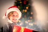 Composite image of child opening his christmas present — Stock Photo