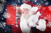 Composite image of santa claus carrying sack — Stock Photo