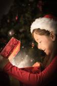 Composite image of little girl opening a magical christmas gift — Fotografia Stock