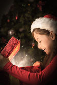 Composite image of little girl opening a magical christmas gift — Stok fotoğraf
