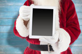 Composite image of santa claus showing tablet pc — Stock Photo