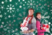 Composite image of couple holding lots of presents — Stock Photo