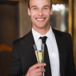 Handsome man holding flute of champagne — Stock Photo #57250055