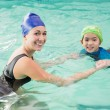 Cute little boy learning to swim with coach — Stock Photo #57250151