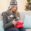 Blond woman opening a gift sitting on a sofa — Stock Photo #57250835
