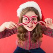 Happy little girl in santa hat holding candy canes — Stock Photo #57251229