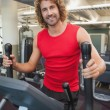 Handsome young man working out on x-trainer — Stock Photo #57251319