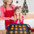 Festive mother and daughter making christmas cookies — Stock Photo #57251791