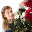 Festive little girl decorating christmas tree — Stok fotoğraf #57252145