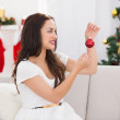 Happy brunette holding a red bauble at christmas — Stock Photo #57252623