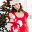 Festive brunette in red dress holding gift at christmas — Stock Photo #57252715