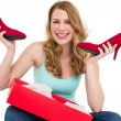 Smiling woman holding up her new shoes — Stock Photo #57252727