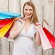 Smiling woman carrying shopping bags over her shoulder — Stock Photo #57253101