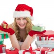 Woman in santa hat laying on the floor while holding gifts — Stok fotoğraf #57253407