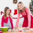 Festive mother and daughter making christmas cookies — Stock Photo #57253659