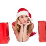 Thoughtful woman lying between shopping bags — Stock Photo #57253897