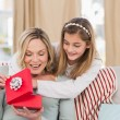 Mother opening christmas gift with daughter — Foto Stock #57253987