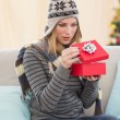 Blond woman opening a gift sitting on a sofa — Stock Photo #57254773